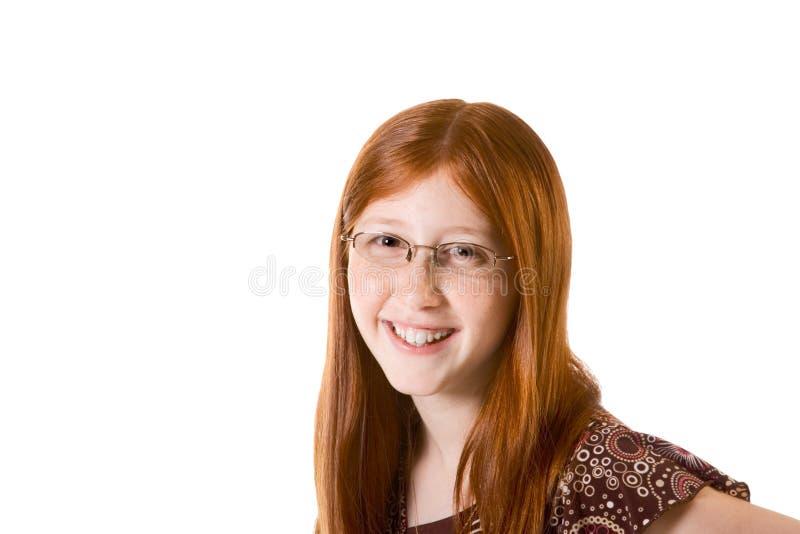 Muchacha preadolescente del redhead cómodo en vidrios fotografía de archivo