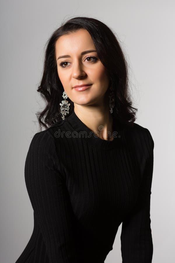 Muchacha preciosa con el pelo negro en un fondo gris imágenes de archivo libres de regalías