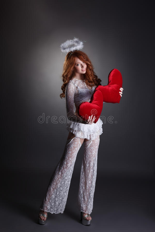 Muchacha preciosa en el traje del ángel que presenta con los corazones fotos de archivo libres de regalías