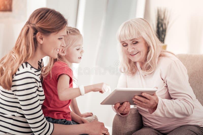 Muchacha preciosa en una camiseta roja que mira un vídeo en una tableta imagen de archivo libre de regalías