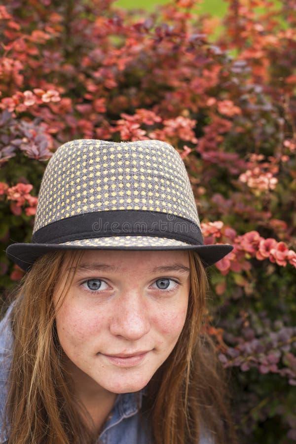 Muchacha preciosa joven en un sombrero, retrato del primer de un jardín de la primavera outdoors foto de archivo