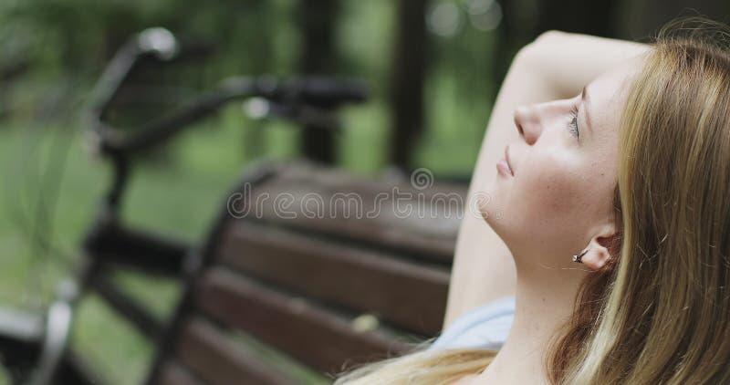 Muchacha preciosa que descansa sobre un banco en el parque en el verano fotos de archivo libres de regalías