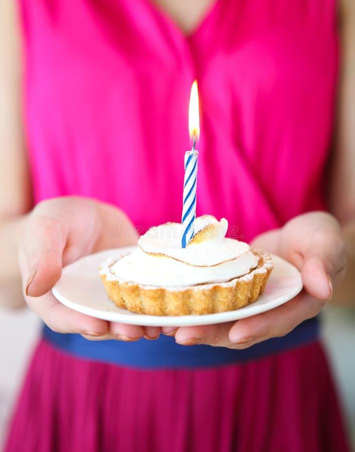 Muchacha preciosa que se sostiene en magdalena de las manos con una vela Cumpleaños p fotos de archivo