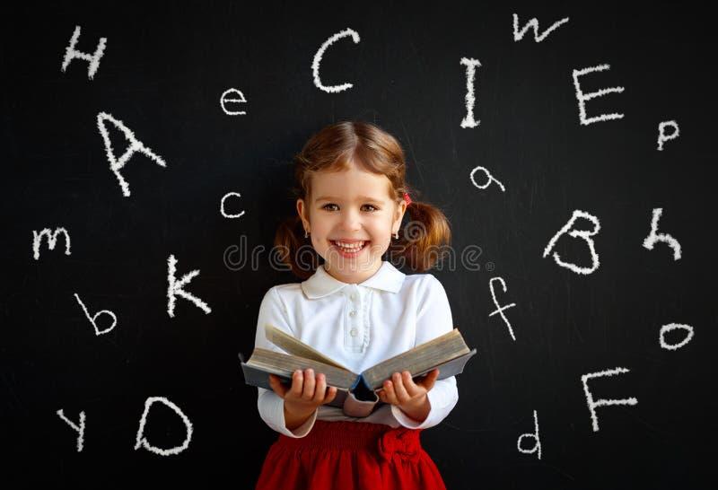 Muchacha preescolar de la colegiala feliz con el libro cerca de la pizarra de la escuela imagen de archivo