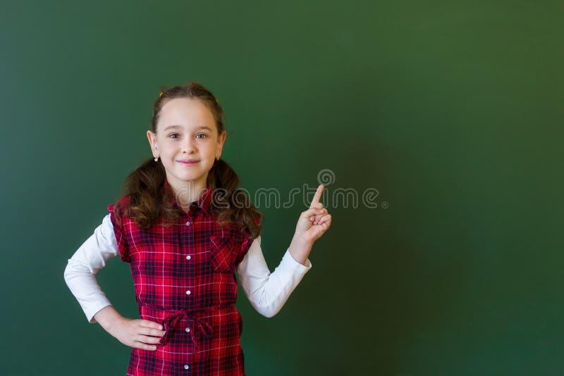 Muchacha preescolar de la colegiala feliz en la situaci?n del vestido de la tela escocesa en clase cerca de una pizarra verde Con foto de archivo libre de regalías