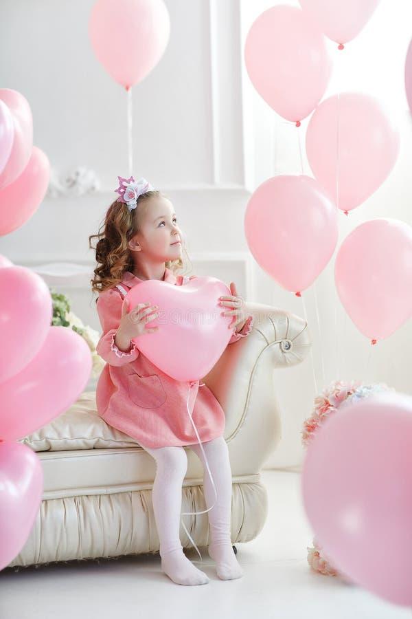 Muchacha preescolar hermosa en un estudio blanco con los globos en forma de corazón rosados fotografía de archivo libre de regalías