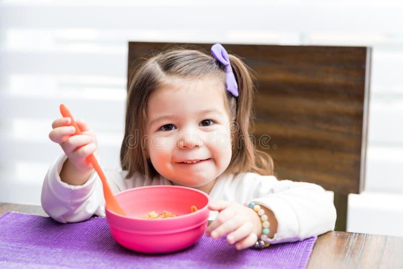 Muchacha preescolar que come la comida en casa foto de archivo libre de regalías