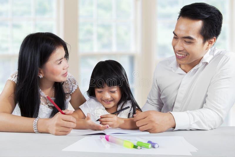 Muchacha preescolar que estudia con los padres fotos de archivo