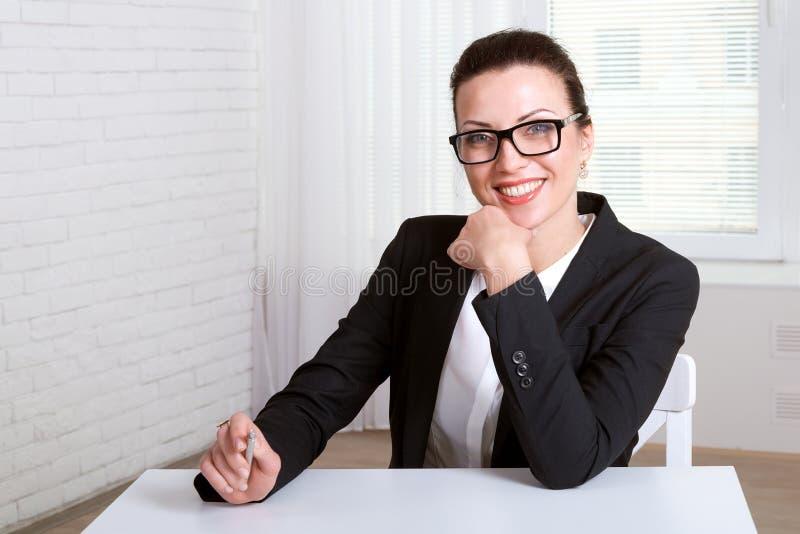 Muchacha principal que descansa su mano en su barbilla y sonrisa fotografía de archivo
