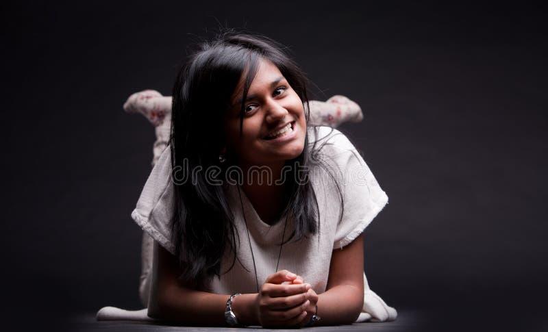 Muchacha propensa en la sonrisa del piso foto de archivo libre de regalías
