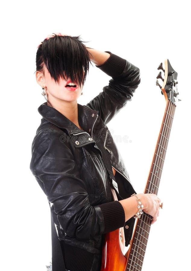 Muchacha punky que sostiene una guitarra y que canta imagen de archivo