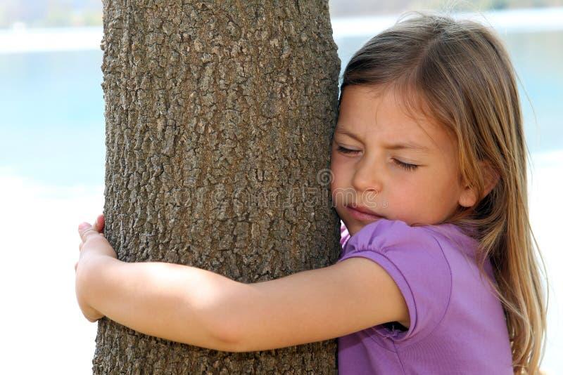 Muchacha que abraza el árbol imagenes de archivo