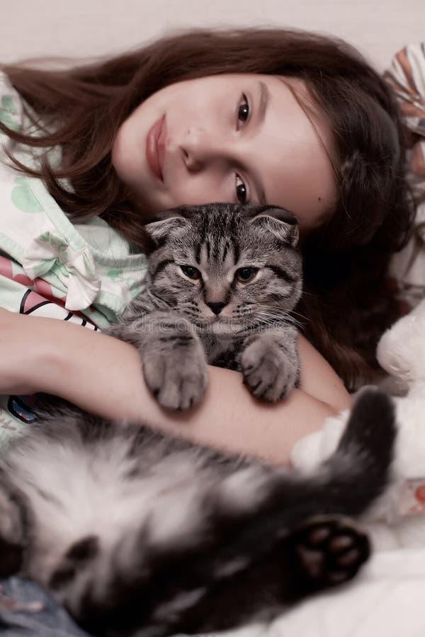 Muchacha que abraza el gatito lindo fotografía de archivo libre de regalías