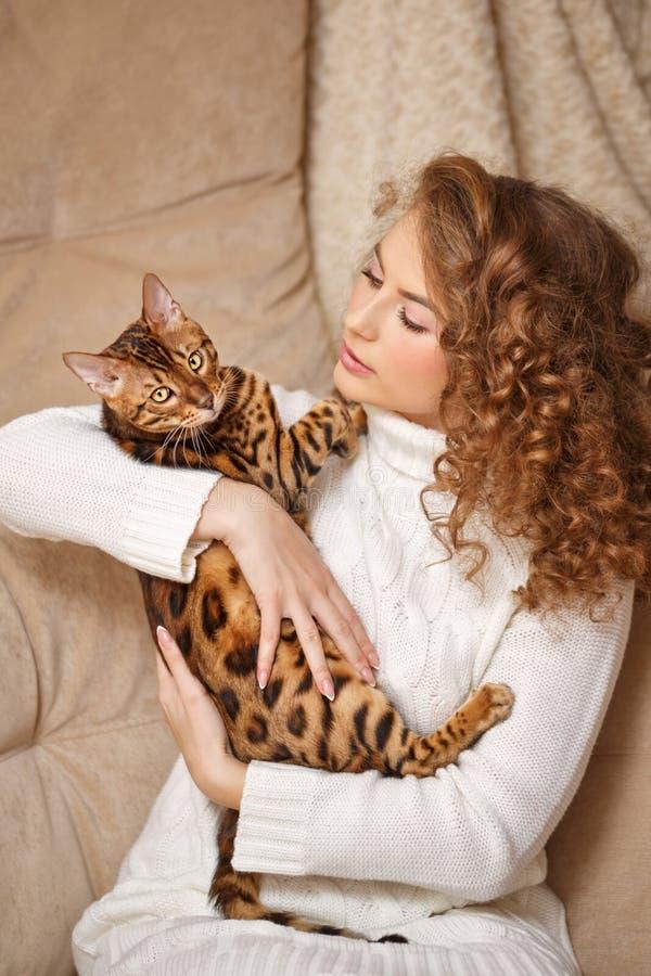 Muchacha que abraza el gato de Bengala imágenes de archivo libres de regalías