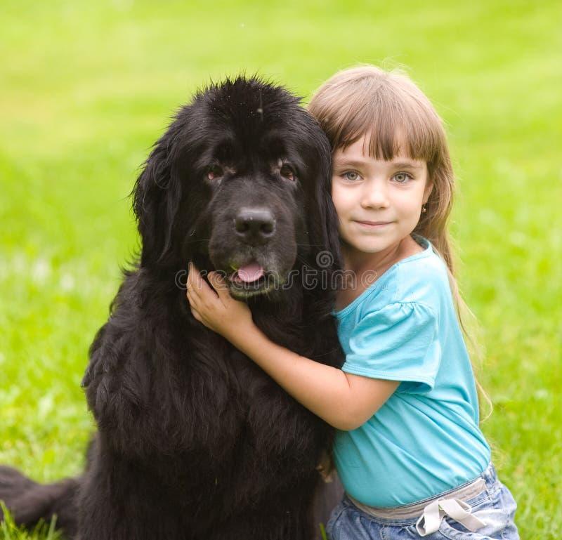 Muchacha que abraza el perro de Terranova foto de archivo