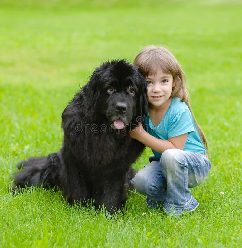Muchacha que abraza el perro de Terranova fotos de archivo libres de regalías