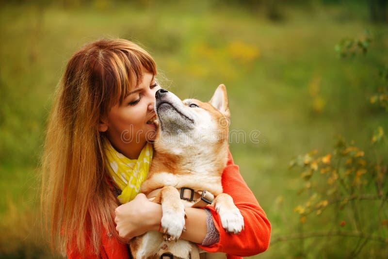 Muchacha que abraza el perro Shiba Inu en parque del otoño fotos de archivo