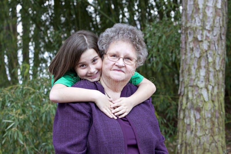 Muchacha que abraza a su bisabuela imagen de archivo libre de regalías