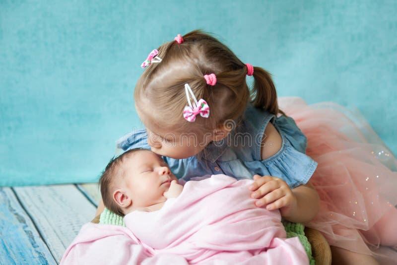Muchacha que abraza a su hermana recién nacida durmiente fotografía de archivo