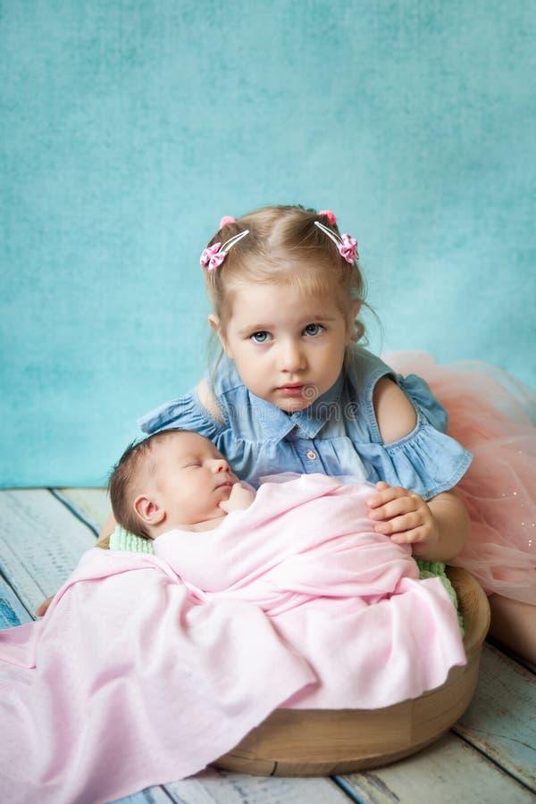 Muchacha que abraza a su hermana recién nacida durmiente fotos de archivo libres de regalías