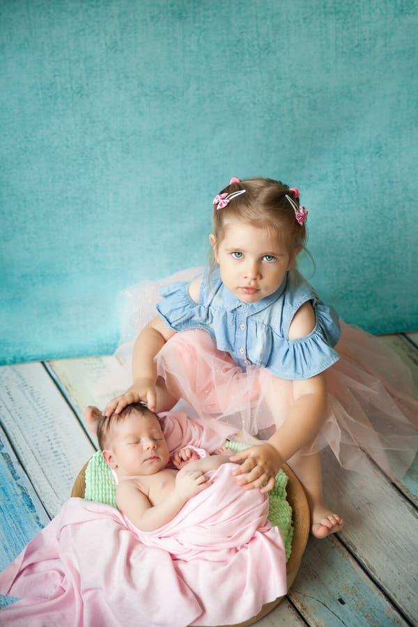 Muchacha que abraza a su hermana recién nacida durmiente foto de archivo libre de regalías