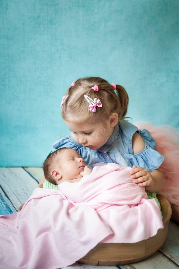 Muchacha que abraza a su hermana recién nacida durmiente foto de archivo