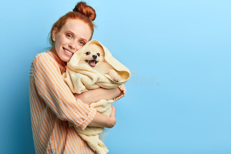 Muchacha que abraza su perro, perro de la tenencia del amante del animal doméstico después de tomar una ducha fotos de archivo libres de regalías