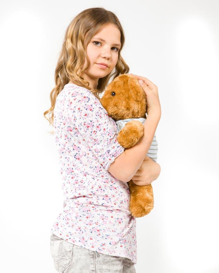 Muchacha que abraza un oso de peluche imagen de archivo