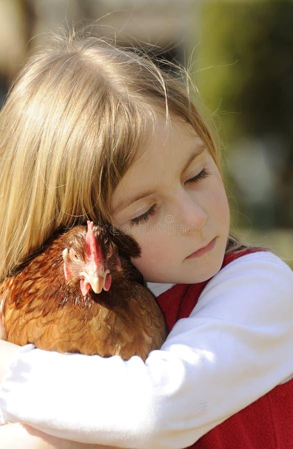 Muchacha que abraza un pollo imagenes de archivo