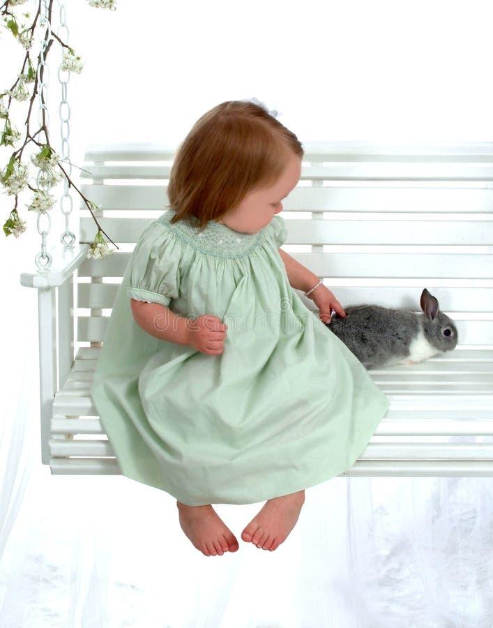 Muchacha que acaricia el conejito en el oscilación foto de archivo libre de regalías