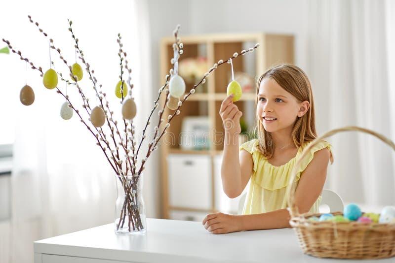 Muchacha que adorna el sauce por los huevos de Pascua en casa imagen de archivo
