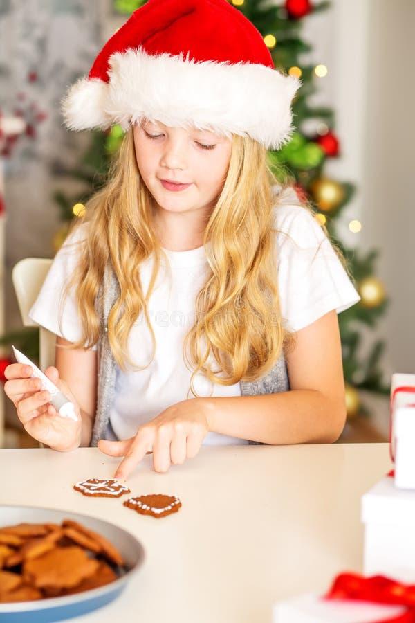 Muchacha que adorna las galletas de la Navidad foto de archivo libre de regalías