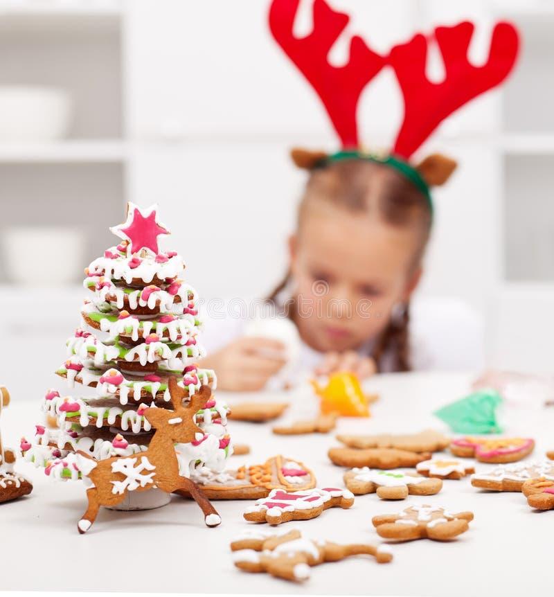 Muchacha que adorna las galletas del pan de jengibre fotografía de archivo