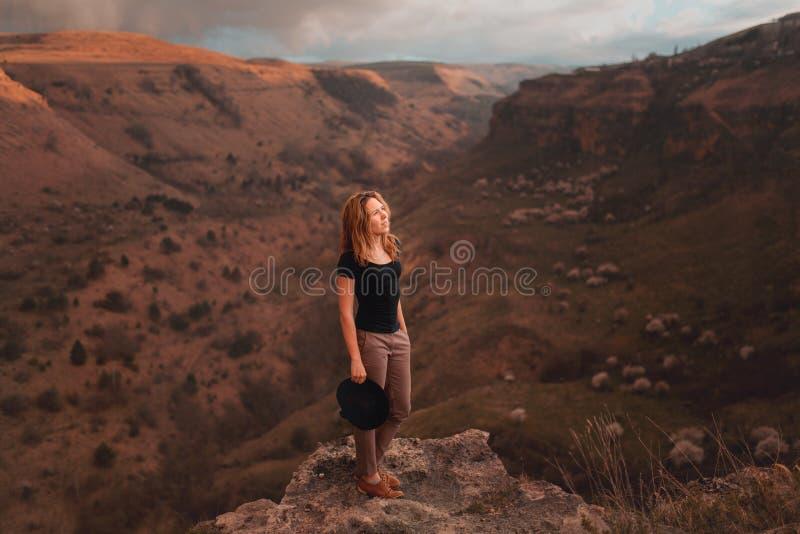 Muchacha que agita su sombrero con su parte posterior que hace frente al valle con las montañas parque nacional del barranco del imagen de archivo