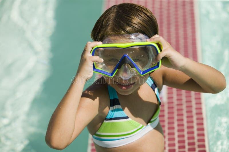 Muchacha (7-9) que ajusta gafas en retrato de la piscina. foto de archivo