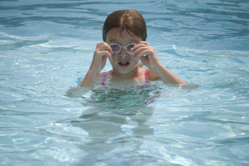 Muchacha que ajusta los anteojos en piscina foto de archivo libre de regalías
