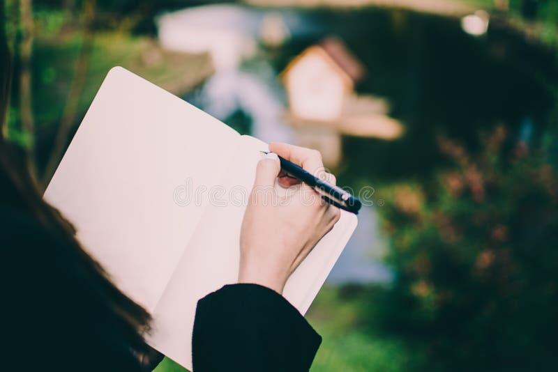 Muchacha que anota sus pensamientos en un cuaderno contra casa borrosa minúscula del cisne en un centro de una charca en un parqu imagen de archivo libre de regalías
