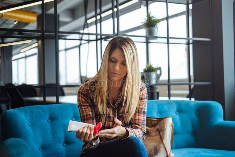Muchacha que aplica la crema en las manos en sala de espera de la oficina foto de archivo libre de regalías