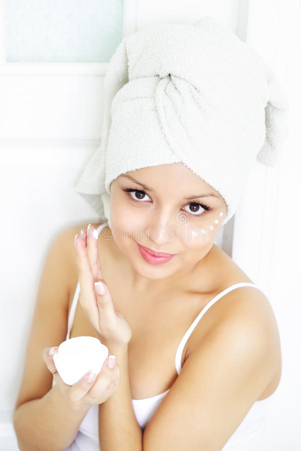 Muchacha que aplica la crema en piel imagen de archivo libre de regalías