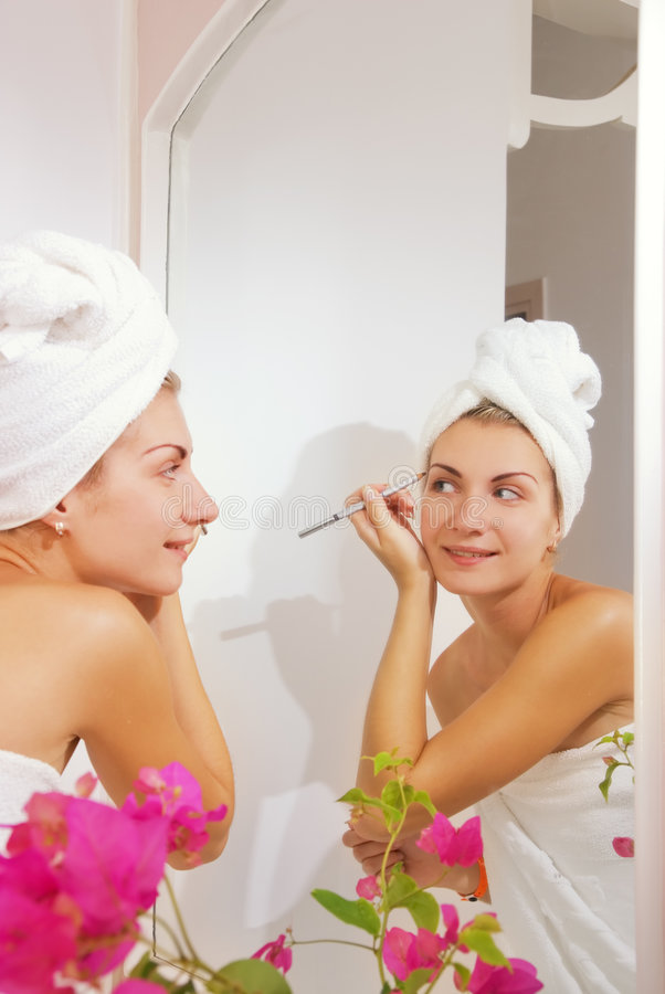 Muchacha que aplica maquillaje fotos de archivo