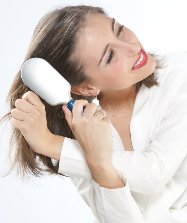 Muchacha que aplica su pelo con brocha fotografía de archivo libre de regalías