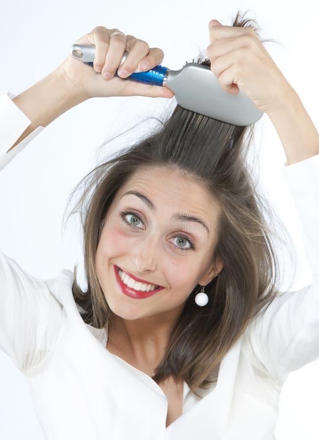 Muchacha que aplica su pelo con brocha fotos de archivo libres de regalías