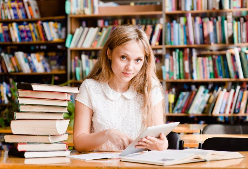 Muchacha que aprende en biblioteca y que lee el eBook en la tableta fotografía de archivo