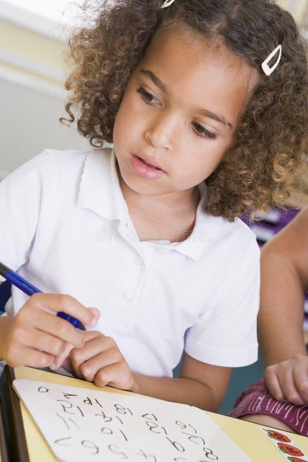 Muchacha que aprende escribir números en clase primaria foto de archivo