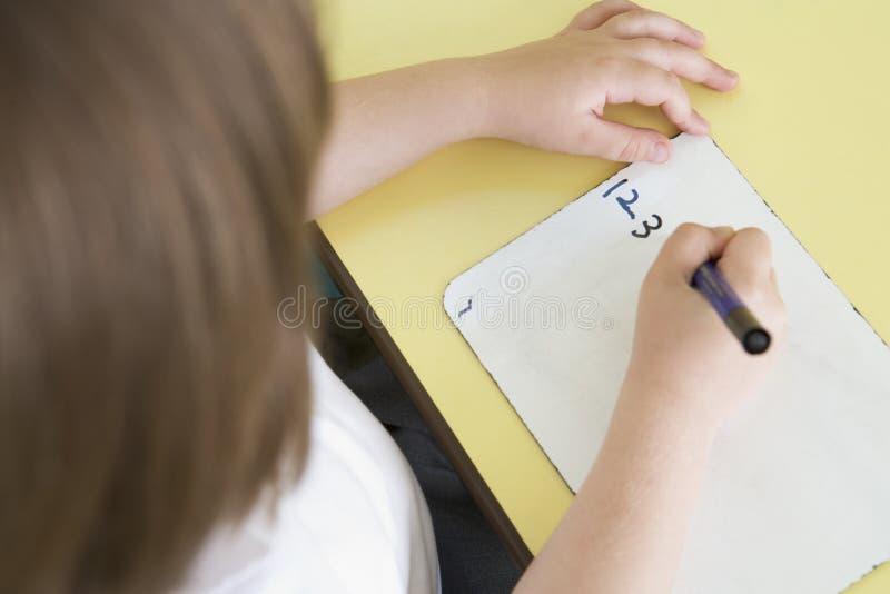 Muchacha que aprende escribir números en clase primaria fotos de archivo