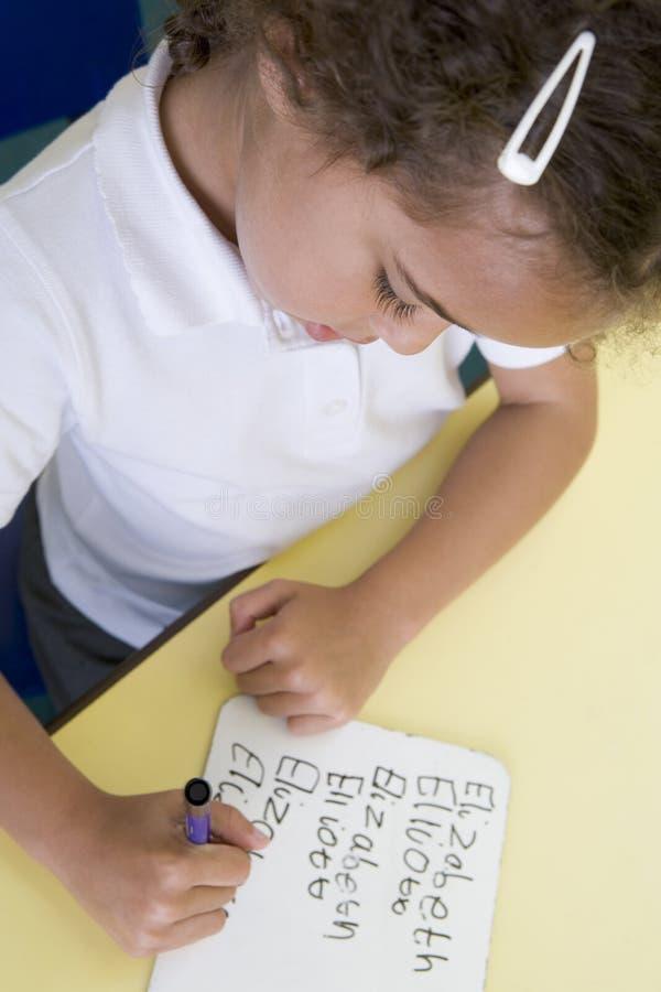 Muchacha que aprende escribir nombre en clase primaria fotos de archivo libres de regalías