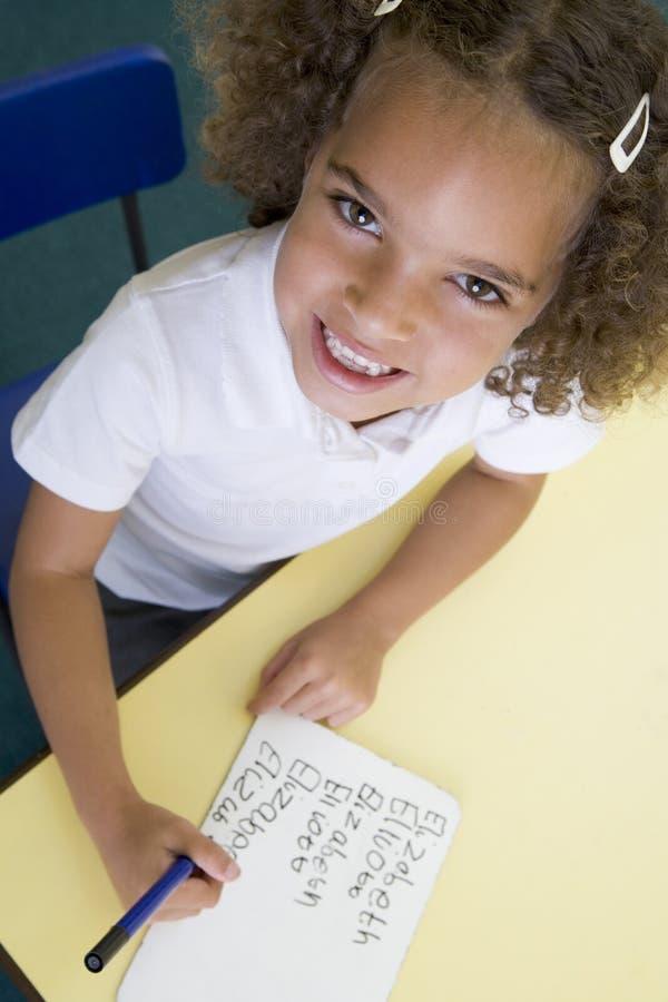 Muchacha que aprende escribir nombre en clase primaria imágenes de archivo libres de regalías