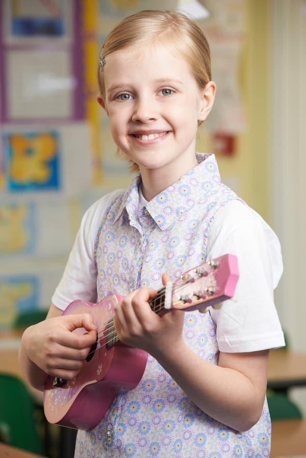 Muchacha que aprende jugar el ukelele en la lección de música de la escuela imagenes de archivo