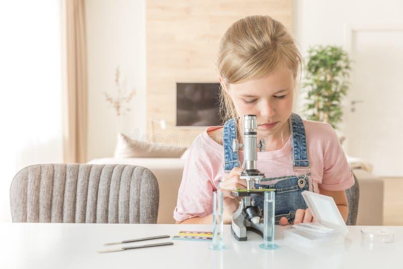 Muchacha que aprende la química que juega con el microscopio en casa imagen de archivo libre de regalías
