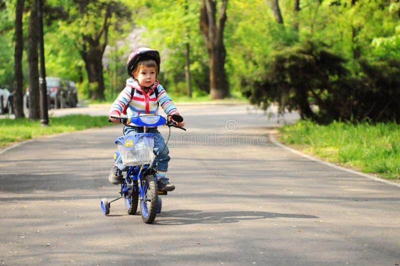 Muchacha que aprende montar la bici foto de archivo